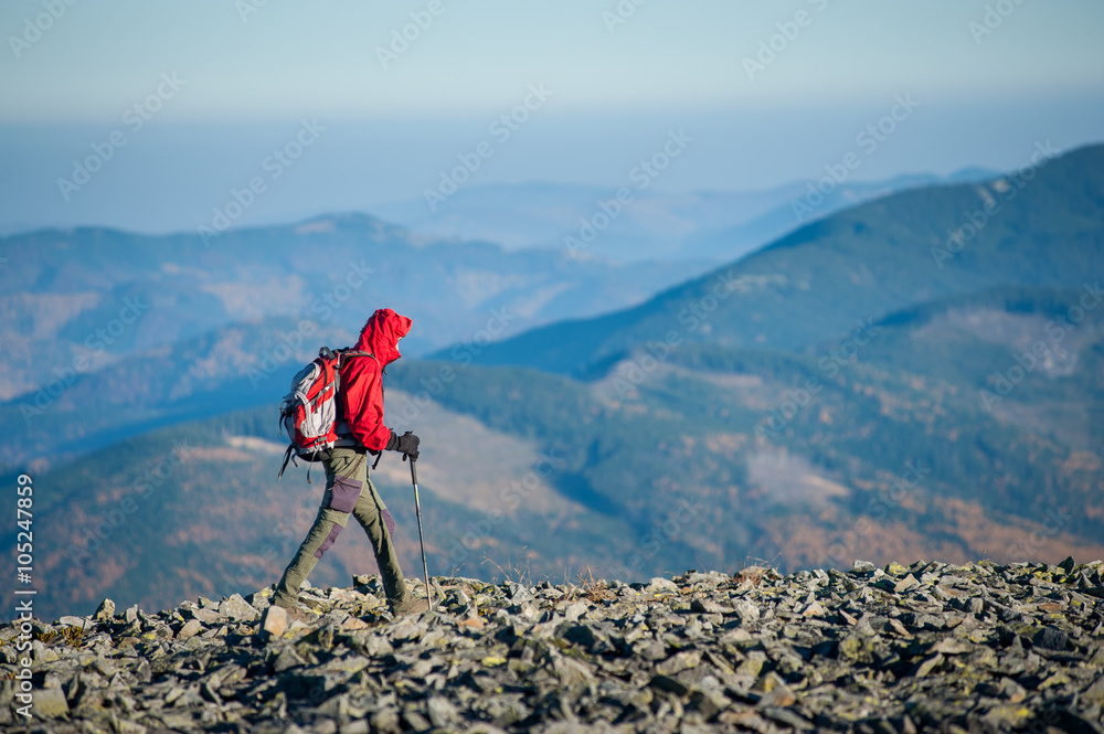 Fototapety, obrazy: Male sportsman tourist walking on the rocky mountain ridge with beautiful mountains on background. Man is wearing red jacket and has trekking sticks and backpack on. Sunny autumn day.