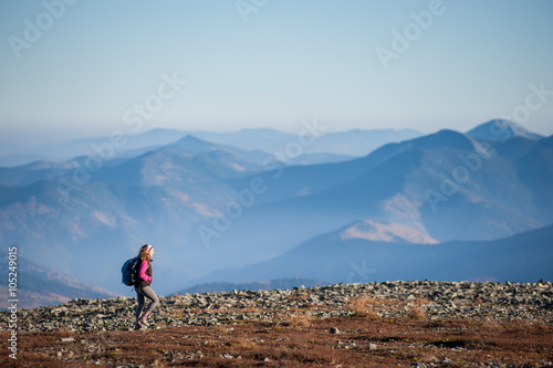 Young tourists is walking on mountain plato with backpack on with beautiful high mountains on background Fototapet