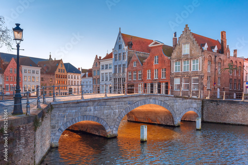 Deurstickers Brugge Scenic city view of Bruges canal with beautiful medieval colored houses and sunny bridge in the morning, golden hour, Belgium