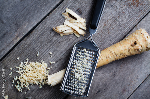 Fotografía Grated horseradish root with grater on wooden gray table.
