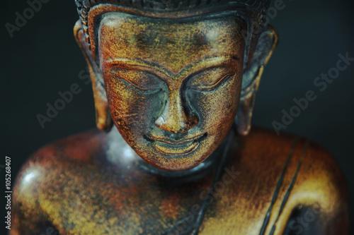 Tuinposter Boeddha Wooden bronze buddha on black blurred background