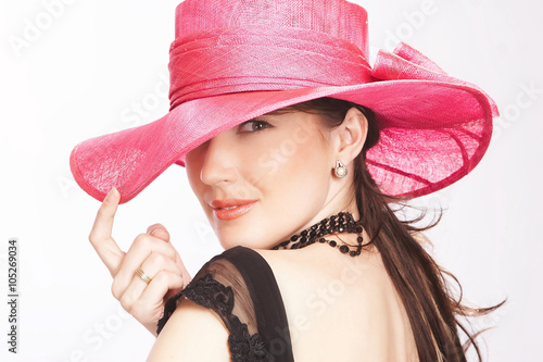 A  woman in a pink summer hat.