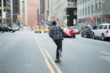Back Figure Of Young Skateboar...