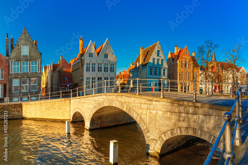 In de dag Brugge Scenic city view of Bruges canal with beautiful medieval colored houses and sunny bridge in the morning, golden hour, Belgium