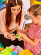 Woman with kid do from colored paper origami in kindergarten .