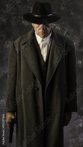 Fotografie, Obraz  Sinister/Low key image of man in overcoat & hat in sinister pose with hand on gu