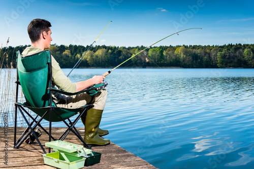 Keuken foto achterwand Vissen Man fishing at lake sitting on jetty