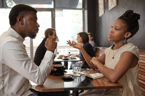 Fotografie, Obraz  African woman and man discussing business ideas at busy cafe
