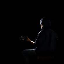 Man Playing Guitar In Studio Play Of Light And Shadow On Black Background With Open Space.
