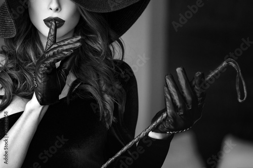 Fototapeta Sexy dominant woman in hat and whip showing no talk obraz