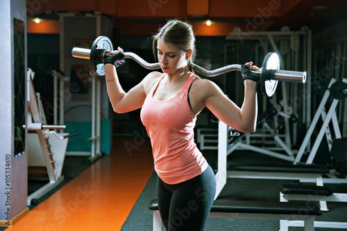 Valokuvatapetti portrait of serious athlete girl holds metal barbell