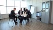 Meeting in the Spacious Office/Team of four businessmen at the meeting in a bright and spacious office. Behind them, large windows, cabinets with folders, a flipchart. Steadycam