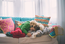 Boy Sleeping On Sofa With Dog