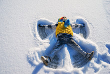 Boy Making A Snow Angel In Snow