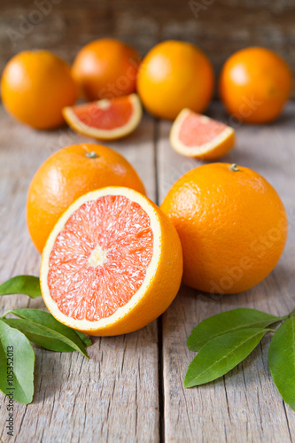 Canvas Prints Fruits Fresh oranges with slices and leaves on wooden background. Selective focus.