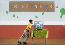 A Boy Pushing A Table Into A Room At The Green Science Fair,
