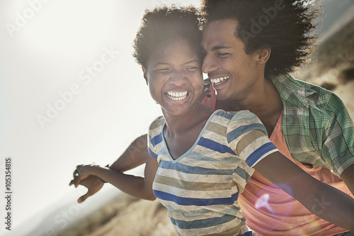 A couple with arms outstretched in a gesture of freedom and excitement, leaning into the breeze,