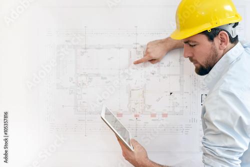 Photo  Bauingenieur mit Tablet vor technischer Zeichnung beim Hausbau // engineer with