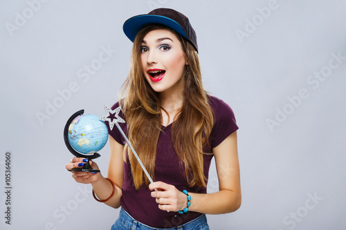 Fotografie, Obraz  Funny girl with little globe at gray background