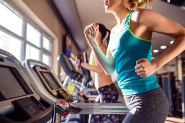Fototapeta samoprzylepna Two fit women running on treadmills in modern gym