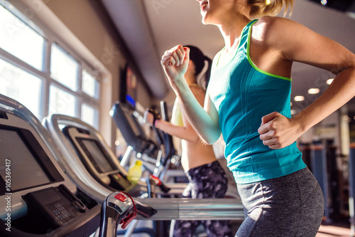 Poster Fitness Two fit women running on treadmills in modern gym