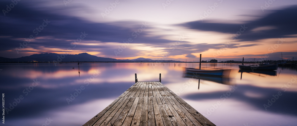 Fototapeta Perspective view of a wooden pier in the lagoon at sunset with perfectly calm water and reflection