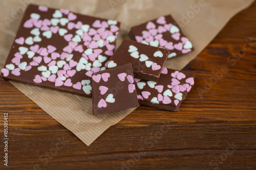 Fotografía  chocolate bar with hearts on a wooden background