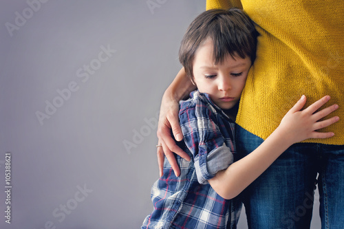 Fototapeta Sad little child, boy, hugging his mother at home