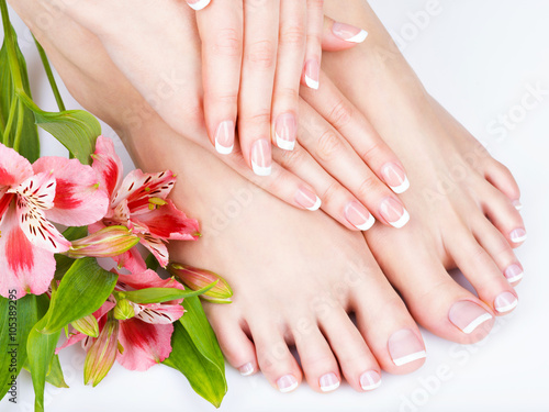 female feet at spa salon on pedicure and manicure procedure - 105389295