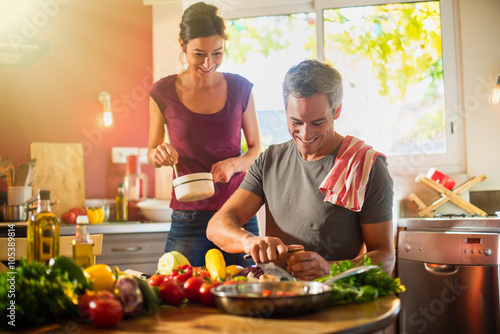 Fotobehang Koken Trendy couple cooking vegetables from the market in the kitchen