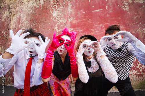 Photo  Four mimes looking through binoculars on a red wall.