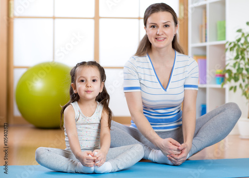 Happy mom and kid daughter spends time in the gym - 105402871