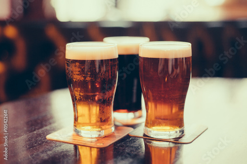 Glasses of light and dark beer on a pub background. Wallpaper Mural