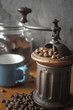 Coffee mill with coffee beans and blurred cup in the table