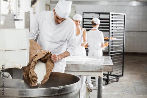 Staande foto Bakkerij Mature Male Baker Pouring Flour In Kneading Machine