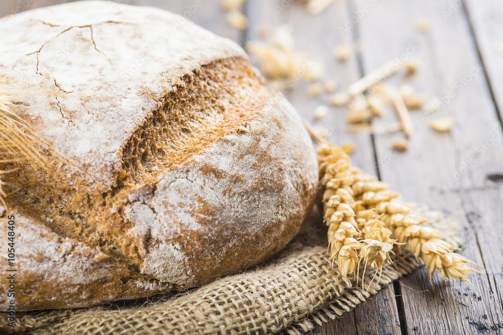 Hogaza de pan de cereales variados sobre arpillera rústica con espigas de trigo y centeno para la comida
