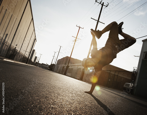 A young man breakdancing on the street of a city, doing a one handed handstand,