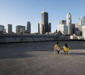 A couple, man and woman sitting in deck chairs on a rooftop overlooking city skyscrapers,