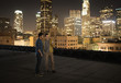 Two men on a rooftop overlooking Los Angeles at night, looking at a smart phone,