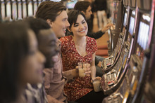 A Group Of People Playing The Slot Machines In A Casino,
