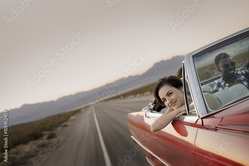 A group of friends in a red open top convertible classic car on a road trip,