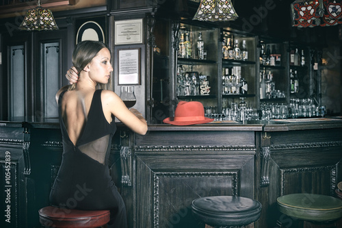 Fotografía  girl at the pub bar with evening dress