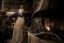 Ironworker Forging Hot Iron In Workshop