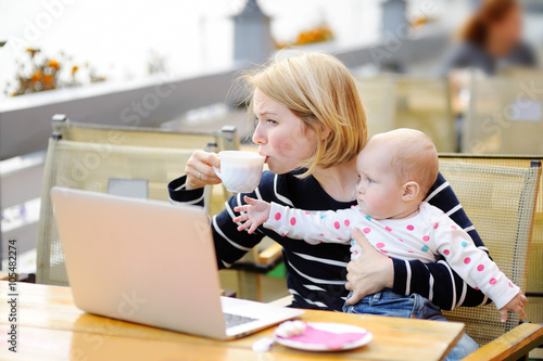 Photo  Tired young mother holding 6-month daughter and drinking coffee