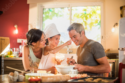 Poster Cuisine 7 years old girl with chef hat is having fun with parents