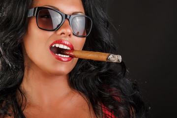 A woman in sunglasses smoki...