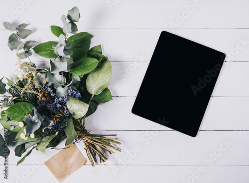 Photo sur Toile Empreintes Graphiques Closeup tablet with a empty blank screen monitor with a bouquet of flowers on white table background with natural wood wooden texture top view, space for publicity information or advertising text
