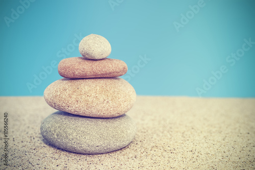 Retro stylized stone pyramid on sand, harmony and balance concep