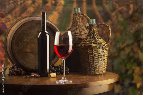 martwa-natura-z-czerwonym-winem-i-balonami-do-wina-na-tle-winnicy