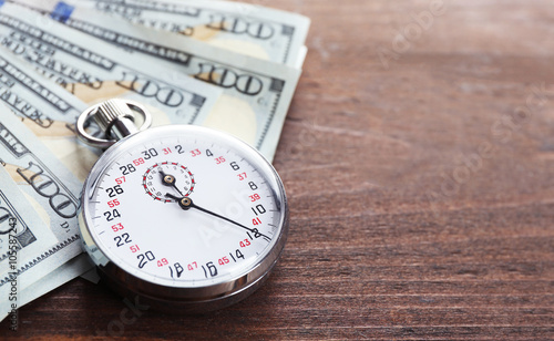 Wall Murals Northern Europe Stopwatch with dollar banknotes on wooden background. Time is money concept